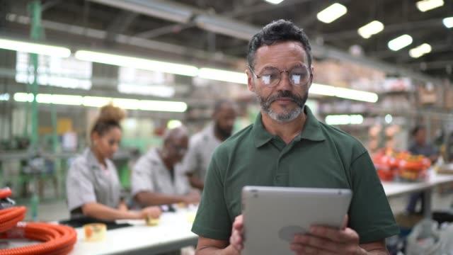 stockvideo's en b-roll-footage met portret van de mens met behulp van tablet in de industrie - productielijn werker