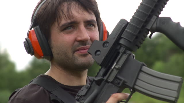 cu portrait of man wearing ear protectors and holding m4 rifle, stowe, vermont, usa - national rifle association stock videos & royalty-free footage