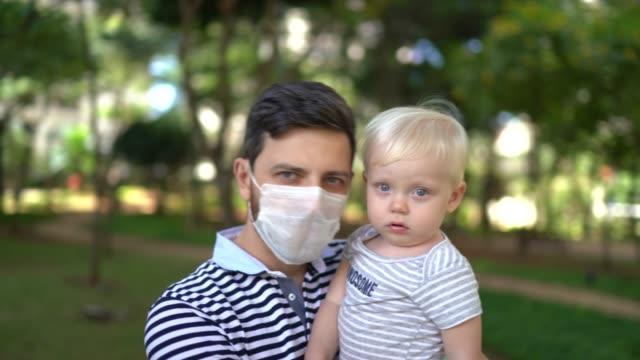 vidéos et rushes de verticale d'homme utilisant le masque de visage portant son fils - famille monoparentale