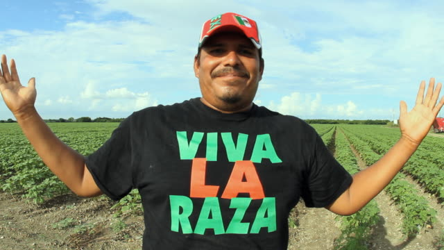 MS Portrait of man wearing Hispanic cap and 'Viva la Raza' t-shirt on field / Homestead, Florida, USA