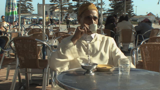 t/l ms portrait of man wearing jellaba sipping espresso in open air cafe, essaouira, morocco - moroccan culture stock videos & royalty-free footage
