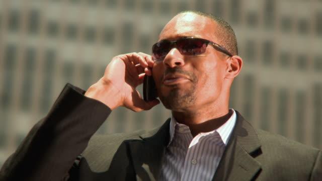 cu shaky portrait of man wearing sunglasses, talking on mobile phone outdoors, jacksonville, florida, usa - ziegenbart stock-videos und b-roll-filmmaterial