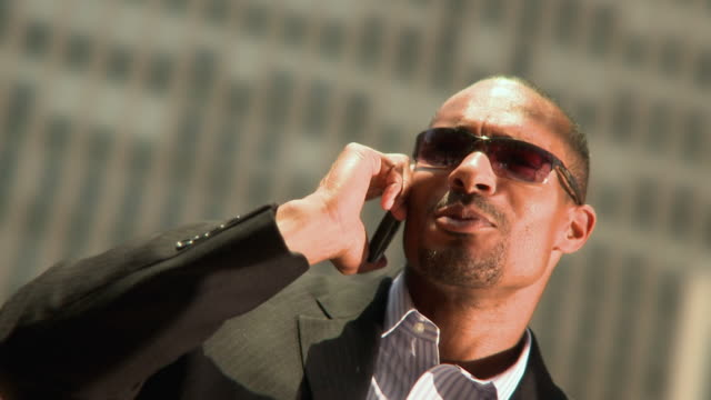 cu shaky portrait of man wearing sunglasses, talking on mobile phone outdoors, jacksonville, florida, usa - goatee stock videos & royalty-free footage