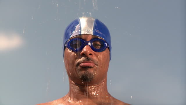 slo mo cu portrait of man wearing swimming cap and goggles with water pouring over his head, jacksonville, florida, usa - swimming cap stock videos & royalty-free footage