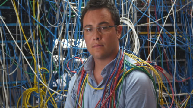 ms zi portrait of man with cables around neck, in front of server covered in cables, sydney, australia - excess stock videos & royalty-free footage