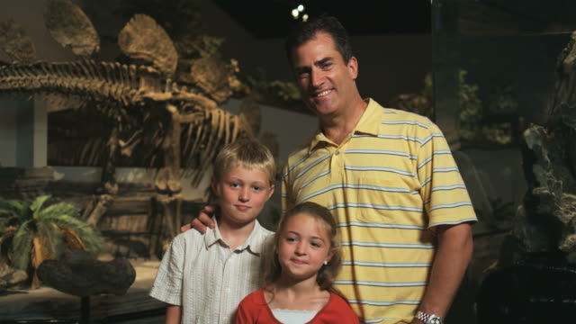 ms pan portrait of man with daughter (8-9) and son (10-11) in natural history museum, lehi, utah, usa - lehi stock videos & royalty-free footage