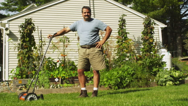 ws portrait of man with lawn mower with vegetable garden and house in background, manchester, vermont, usa - gärtnern stock-videos und b-roll-filmmaterial