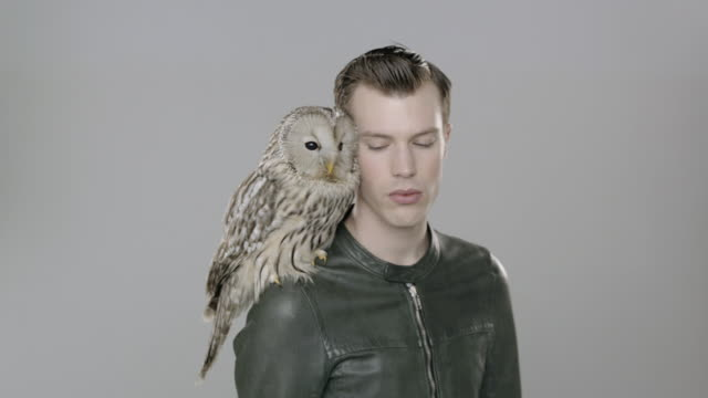 portrait of man with owl perched on shoulder looking up to camera as he turns in place - レザージャケット点の映像素材/bロール