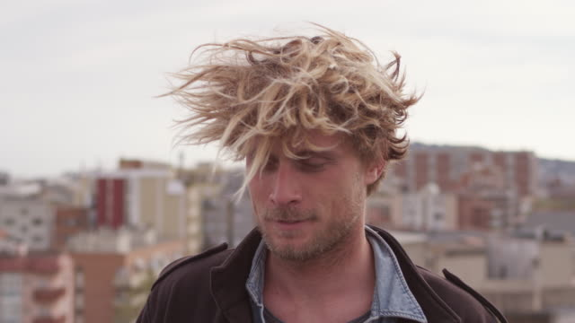 portrait of man with tousled hair against city - windswept stock videos & royalty-free footage