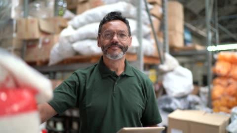 porträt des mannes, der im lager / in der industrie arbeitet - manufacturing occupation stock-videos und b-roll-filmmaterial