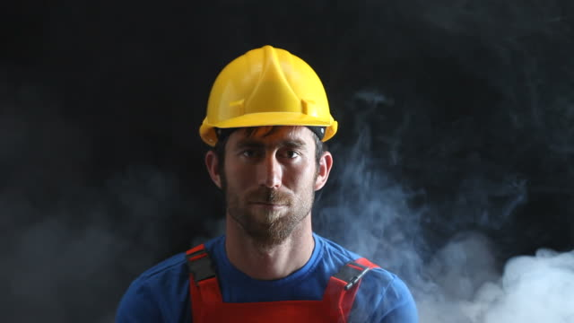 portrait of manual worker in dark and fog - construction worker stock videos and b-roll footage