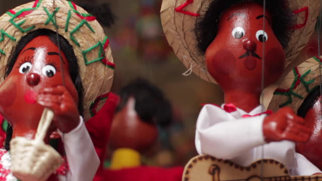 portrait of marionettes, made of wood, hanging at mercado de artesan'as de la ciudadela market in mexico city, mexico. the characters are couples of... - マリオネット点の映像素材/bロール