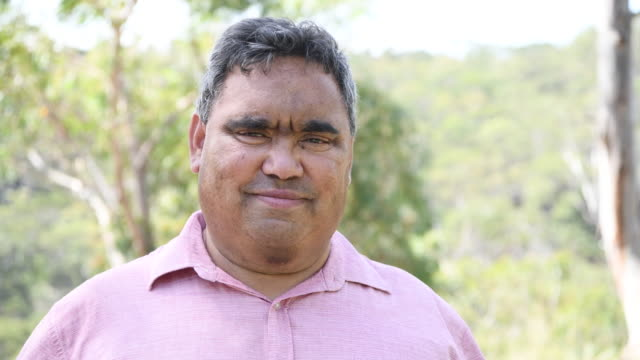 portrait of mature aboriginal man smiling towards camera - australian aboriginal culture stock videos and b-roll footage