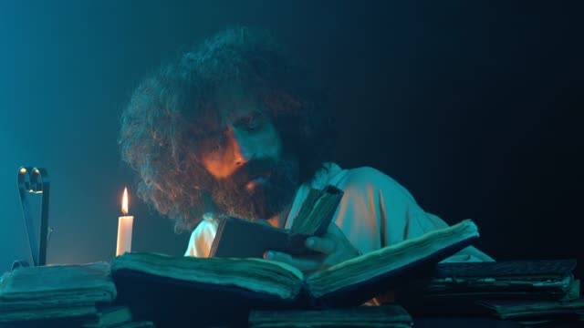 UHD Portrait Of Mature Adult Man Reading Antique Book With Candlelight