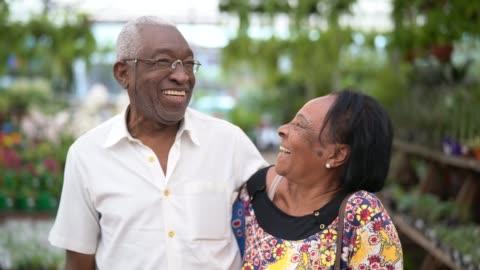 porträtt av äldre afrikanska par kund på blomstermarknaden - aktiva pensionärer bildbanksvideor och videomaterial från bakom kulisserna