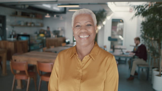 portrait of mature business woman in modern coworking space - short hair stock videos & royalty-free footage