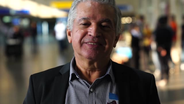 portrait of mature businessman at airport - solo un uomo anziano video stock e b–roll