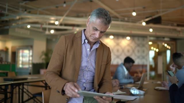 vidéos et rushes de verticale d'homme d'affaires mûr sur une réunion utilisant la tablette numérique - culture d'entreprise