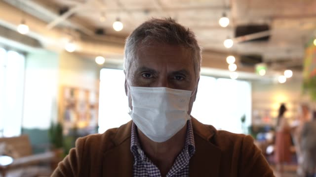 portrait of mature businessman with mask at work - respiratory system stock videos & royalty-free footage