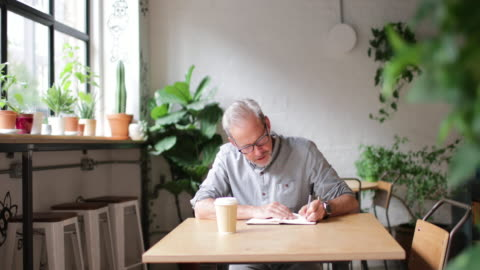 portrait of mature businessman working in a cafe - smart casual stock videos & royalty-free footage