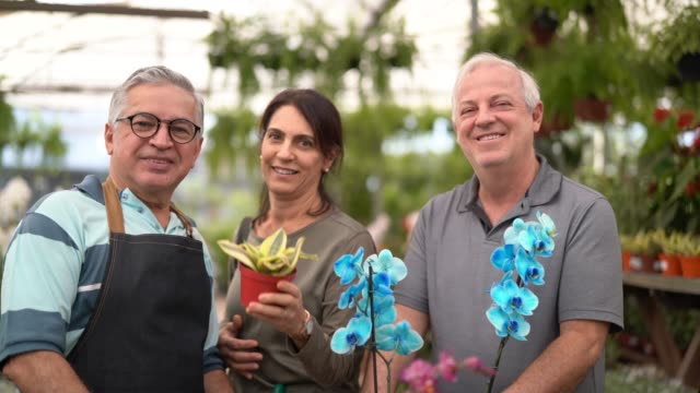 portrait of mature couple customer with salesman at flower market - non us location stock videos & royalty-free footage