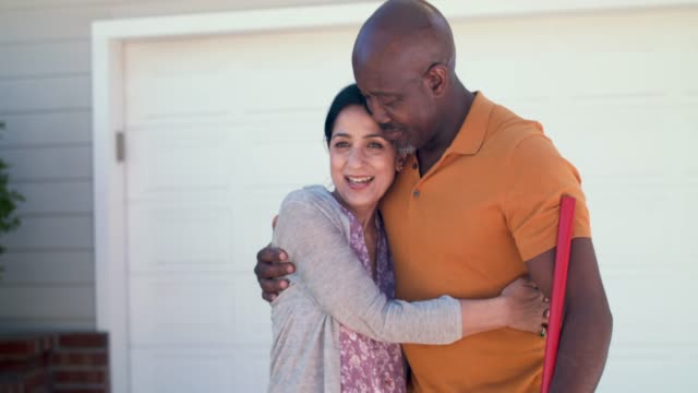 portrait of mature couple embracing in driveway of their home - mature couple stock videos & royalty-free footage