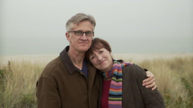 CU Portrait of mature couple embracing on beach / Sea Bright, New Jersey, USA