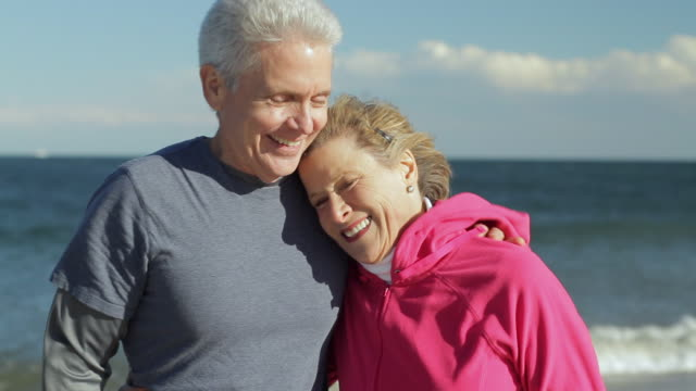 MS Portrait of mature couple smiling on beach / Sea Bright, New Jersey, USA