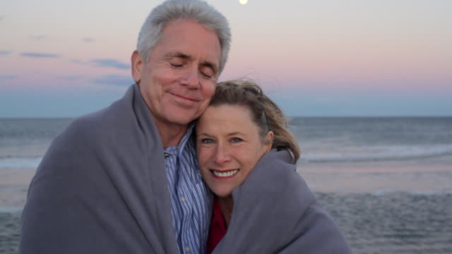 MS Portrait of mature couple wrapped in blanket on beach side / Sea Bright, New Jersey, USA