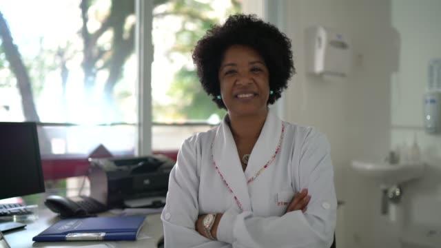 vídeos de stock, filmes e b-roll de retrato de médica madura no consultório médico - confiança
