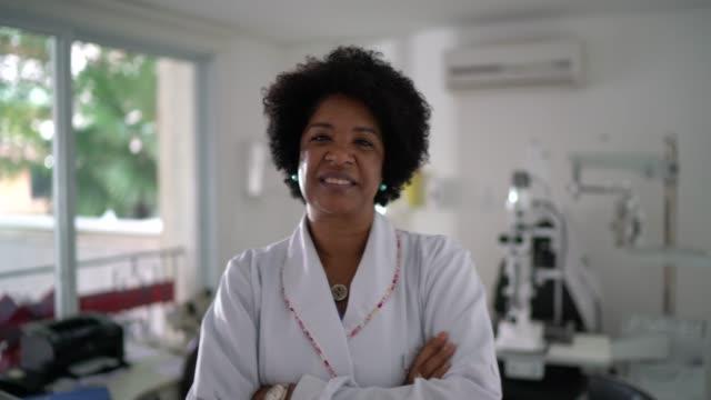 vídeos de stock, filmes e b-roll de retrato de médica madura no consultório médico - braços cruzados