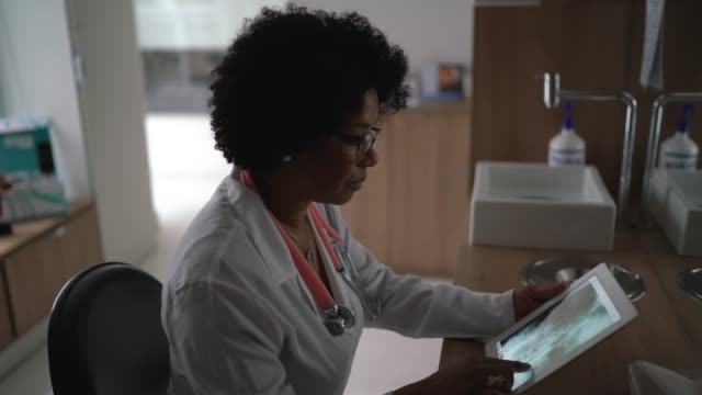 portrait of mature female doctor using digital tablet at medical office - one mature woman only stock videos & royalty-free footage