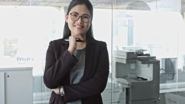 事務所に立っている成熟したマレー中国人実業家の肖像画 - 腕組み点の映像素材/bロール