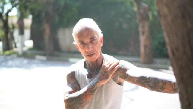 portrait of mature men stretching in street - tattoo stock videos & royalty-free footage