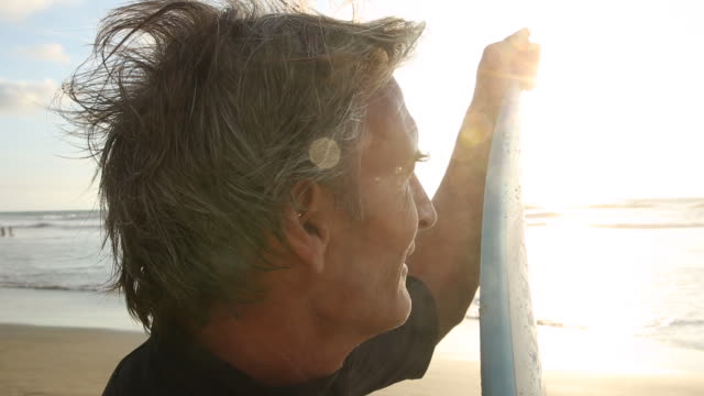 Portrait of mature surfer, on beach at sunrise