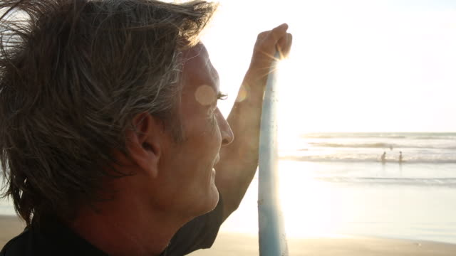portrait of mature surfer, on beach at sunrise - mature men stock videos & royalty-free footage