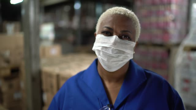 vídeos de stock e filmes b-roll de portrait of mature woman wearing face mask working in warehouse / industry - saúde e segurança ocupacional