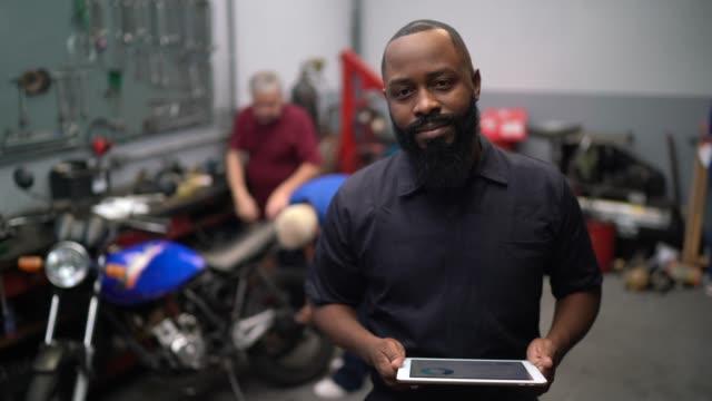 portrait of mechanic man using digital tablet in auto car repair - mechanic stock videos & royalty-free footage