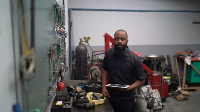 portrait of mechanic man using digital tablet in auto car repair - technician stock videos & royalty-free footage