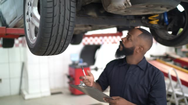 vídeos y material grabado en eventos de stock de retrato del mecánico que trabaja en la reparación automática - mecánico de coches