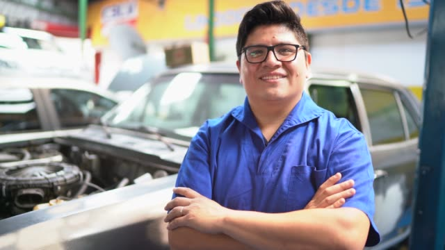 portrait of mechanic standing with arms crossed in front of a car - mexican ethnicity stock videos & royalty-free footage
