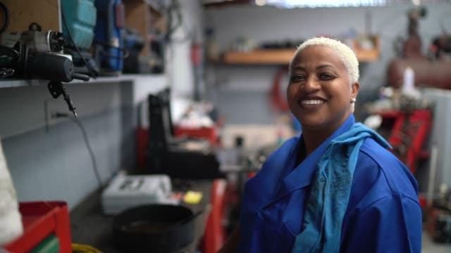 vidéos et rushes de verticale de la femme mécanique dans la réparation de voiture d'automobile - ouvrier à la chaîne