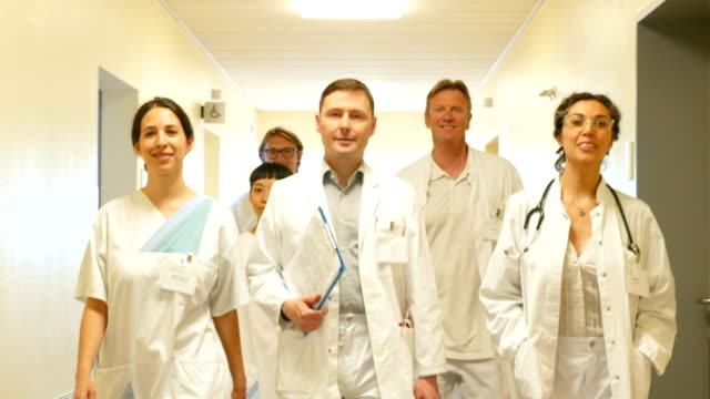 portrait of medical team walking in corridor - medical occupation stock videos and b-roll footage