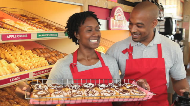 ms portrait of mid adult couple in donut shop smiling, kissing/ richmond, virginia, usa - bagel stock videos & royalty-free footage