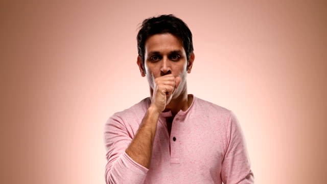 cu portrait of mid adult man coughing while standing against pink background / new delhi, delhi, india - mid adult men stock videos & royalty-free footage