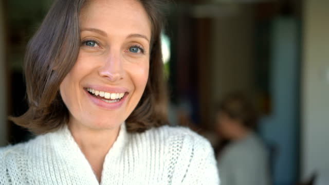 vídeos de stock e filmes b-roll de portrait of mid adult woman smiling at home - contente