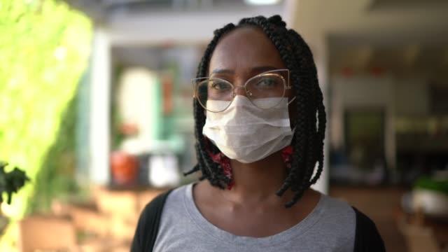 vídeos de stock, filmes e b-roll de retrato de mulher adulta média usando máscara facial em casa - máscara de proteção