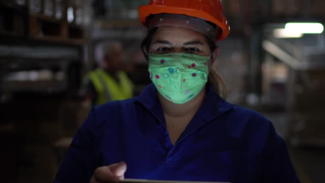portrait of mid adult woman wearing face mask using digital tablet - working at warehouse / industry - health and safety stock videos & royalty-free footage