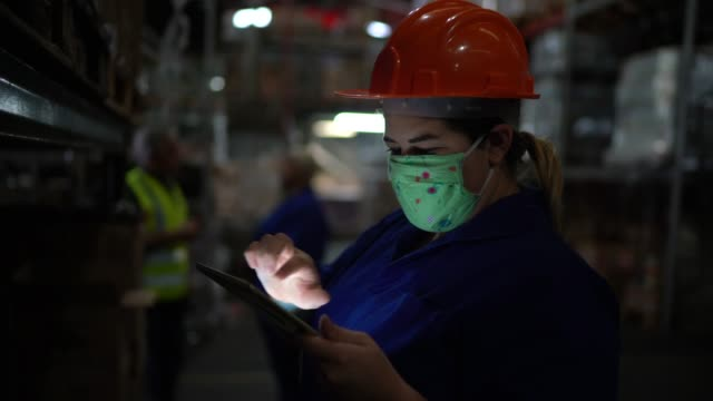 portrait of mid adult woman wearing face mask using digital tablet - working at warehouse / industry - officina video stock e b–roll