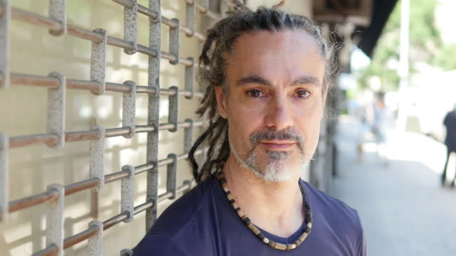 portrait of mid age rastafarian man facing camera outdoors in the city. people lifestyle background - rastafarian stock videos & royalty-free footage